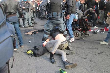 I due ragazzi bloccati e pestati per terra a Piazza Barberini durante la manifestazione del 12 aprile a Roma. Fotografia di Checchino Antonini