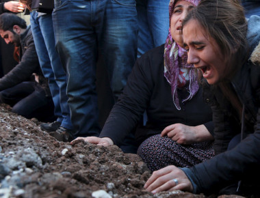 Relatives of Siyar Salman mourn over his grave during a funeral ceremony in the Kurdish dominated southeastern city of Diyarbakir, Turkey