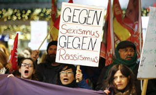 """Women shout slogans and hold up a placard that reads """"Against Sexism - Against Racism"""" as they march through the main railway station of Cologne"""