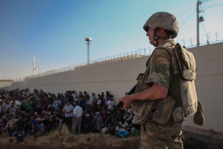 Un soldato turco controlla rifugiati siriani. © Reuters