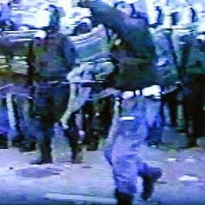 Adriano Lauro (il poliziotto in primo piano) lancia un sasso contro i manifestanti il 20 luglio 2001, a Genova