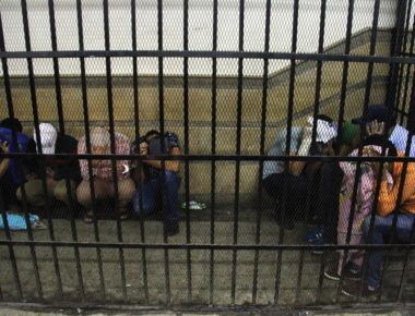 Eight Egyptian men on trial for doing a video prosecutors claimed was of a gay wedding hide their identities as they sit in the defendent's cage during their trial in Cairo on November 1, 2014. The video, filmed aboard a Nile riverboat, shows what prosecutors said was a gay wedding ceremony, with two men in the centre kissing, exchanging rings and cutting a cake with their picture on it. The Egyptian court jailed the eight men for three years. AFP PHOTO / STR