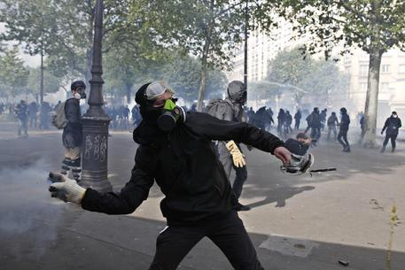 epa06704977 A masked youth protester throws stones in clashes with French police forces during a demonstration of workers from the private and public sectors as well as labor unions on the occasion of the annual May Day marches on the International Workers' Day, in Paris, France, 01 May 2018. French unions led a movement of strikes to protest against government reforms in the public services.  EPA/YOAN VALAT