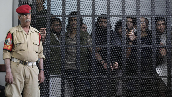 A Yemeni military policeman stands guard as suspected Yemeni militants stand behind bars during a court session at a state security court in Sanaa, Yemen, Wednesday, Oct. 2, 2013. Officials say the court Wednesday sentenced five militants to up to ten years in prison for their role in the May 2012 suicide attack that struck a military parade and killed more than 90 conscripts in the capital Sanaa. Three former top military officials, including a nephew of the former president, were accused of negligence in the suicide attack. (AP Photo/Hani Mohammed)