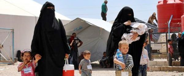 epa07623503 Wives of Islamic state fighters (IS) walk with their children upon their deportation from the al-Hol camp for refugees in al-Hasakah governorate in northeastern Syria on 03 June 2019 (issued 04 June 2019).  According to media reports, the Kurdish authorities in northeast Syria are handing over 800 women and children all of them Syrian, including relatives of Islamic state fighters, to their families in the first such transfer from an overcrowded camp.  EPA/AHMED MARDNLI