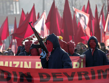 epa05079526 A masked member of an ultra leftist group brandishes an automatic weapon during the funeral of Yeliz Erbay and Sirin Oter, members of an ultra leftist party, killed by Turkish police in an anti-terror operation, in Istanbul, Turkey, 23 December 2015. According to local reports two members of the leftist group were killed and four police officers wounded, in an anti terror operation linked to a roadside bomb attack in Istanbul.  EPA/SEDAT SUNA