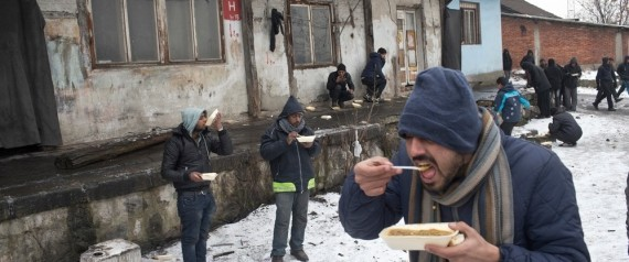 People eat meals outside an abandoned railway warehouse used as shelter by refugees in Belgrade, Serbia, Thursday, Jan. 5, 2017.