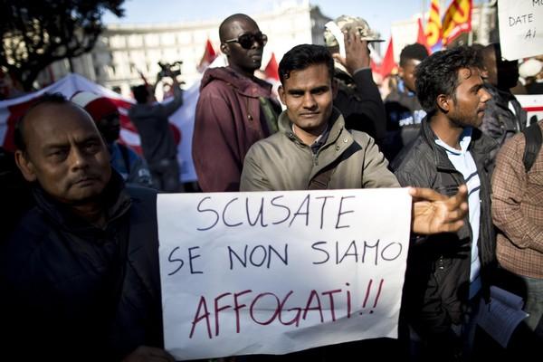 Immigrati partecipano alla manifestazione promossa dai sindacati di base (Cobas, Usb e Cub) per chiedere a gran voce la cancellazione della legge Bossi-Fini, Roma, 18 ottobre 2013 a Roma. Sul cartello la scritta: 'Scusate se non siamo affogati'. ANSA/ GUIDO MONTANI