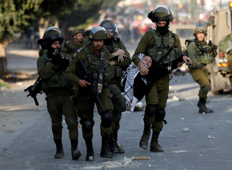Nablus, Cisgiordania, soldati israeliani catturano un giovane manifestante palestinese © Reuters/Mohamad Torokman