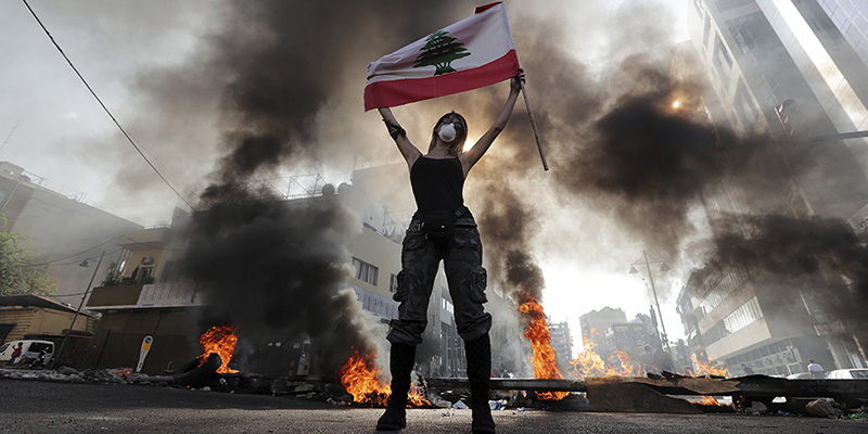 An anti-government protester holds a Lebanese flag while standing in front burning tires that block a road in the town of Jal el-Dib, north of Beirut, Lebanon, Wednesday, Nov. 13, 2019. Lebanese protesters blocked major highways with burning tires and roadblocks on Wednesday, saying they will remain in the streets despite the president's appeal for them to go home. (AP Photo/Hassan Ammar)