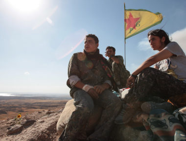 KOBANE, SYRIA - JUNE 20: (TURKEY OUT) A Kurdish People's Protection Units, or YPG fighters stand near a check point in the outskirts of the destroyed Syrian town of Kobane, also known as Ain al-Arab, Syria. June 20, 2015. Kurdish fighters with the YPG took full control of Kobane and strategic city of Tal Abyad, dealing a major blow to the Islamic State group's ability to wage war in Syria. Mopping up operations have started to make the town safe for the return of residents from Turkey, after more than a year of Islamic State militants holding control of the town. (Photo by Ahmet Sik/Getty Images)